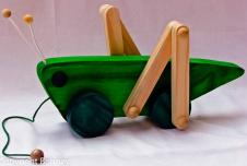 Brinquedo para puxar imitando um Grilo. Ao ser puxado as pernas fazem um movimento para frente e para trás típico do grilo ao caminhar. Fabricado com madeira maciça e pintada com anilina verde. Faixa etária: Acima de 9 meses.